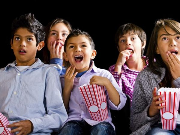 Group of kids watching a film at the movies